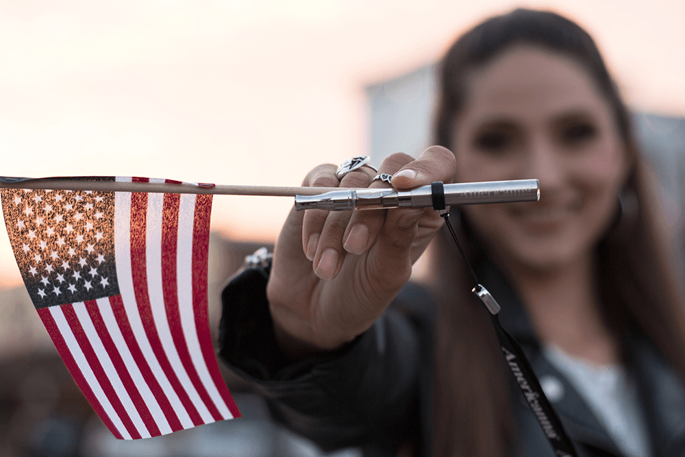 Americanna blog - The best cannabis vapes for veterans can be found right here in Sacramento. Woman with vape pen and US flag.